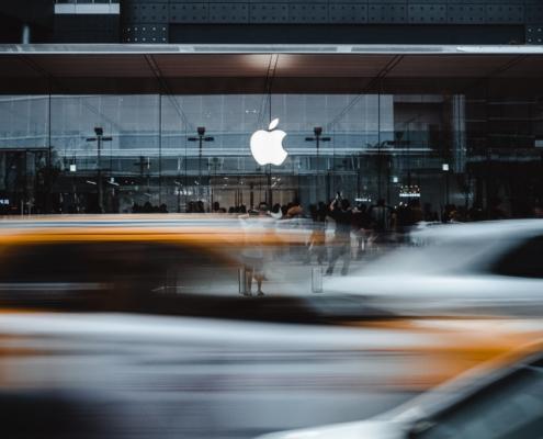 Autos fahren an einem Apple Store vorbei.